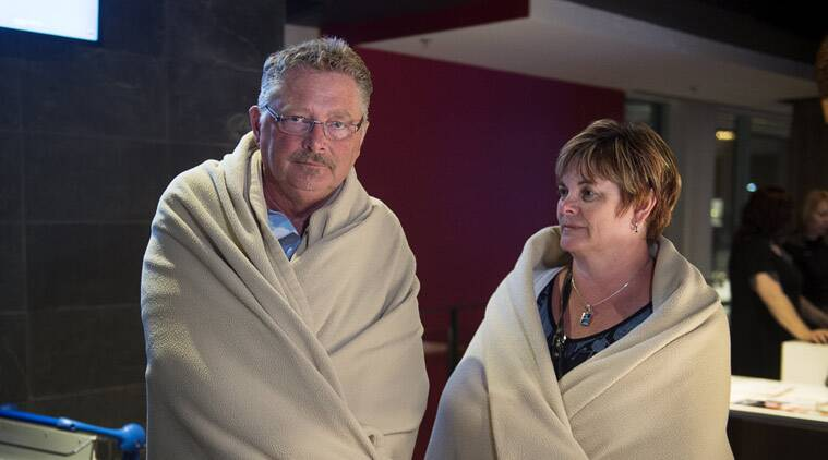 Passengers Randy Hall, left, and Lianne Clark, from Mount Uniacke, Canada stand waiting at an airport hotel after Air Canada flight 624 left the runway on landing at Stanfield International Airport in Halifax on Sunday, March. 29, 2015. Air Canada says at least 22 people were taken to hospital. The flight had 132 passengers and five crew members. (AP Photo/The Canadian Press, Andrew Vaughan)