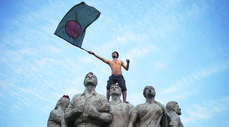 A Bangladeshi fan waves the flag standing atop a sculpture following their big win in the World Cup — beating England by 15 runs. (Source: AP)