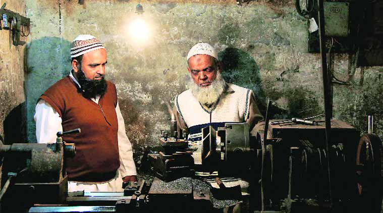 Zufiqar Nasir, who survived the Hashimpura massacre, with father Abdul Jabbar at their small workshop in Meerut.(Express photo by: Gajendra Yadav)