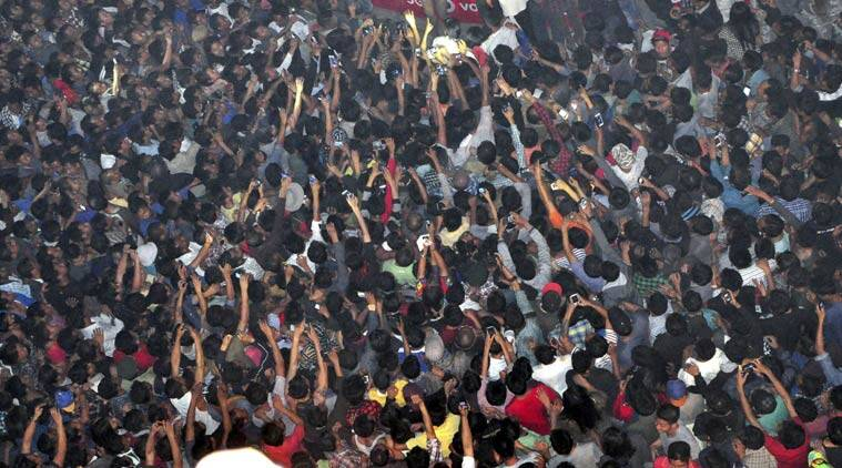 In this Thursday, March 5, 2015 photo, members of a mob raise their hands to take photos of a man, top center, accused of rape after he was lynched and hung in the city landmark Clock Tower in Dimapur, in the northeastern Indian state of Nagaland. (Source: AP)