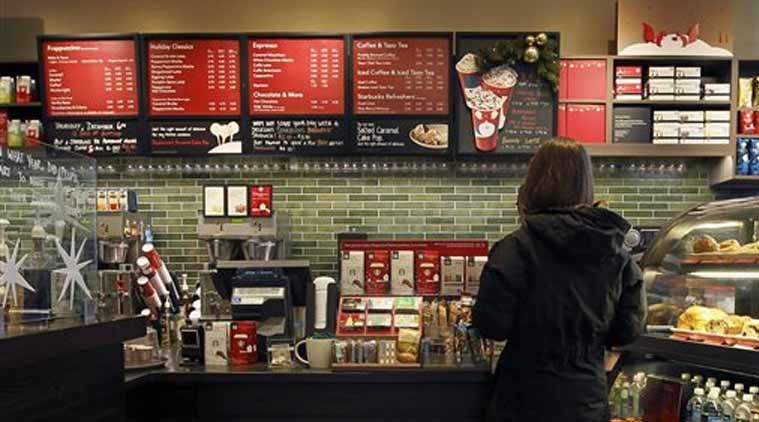 In this Dec. 5, 2012 file photo, a customer places an order at a Starbucks in Chicago. Areas by cash registers are often crowded with little extras in part because the closer a customer is to an item, the more likely they are to make an impulse buy. (Source: AP)
