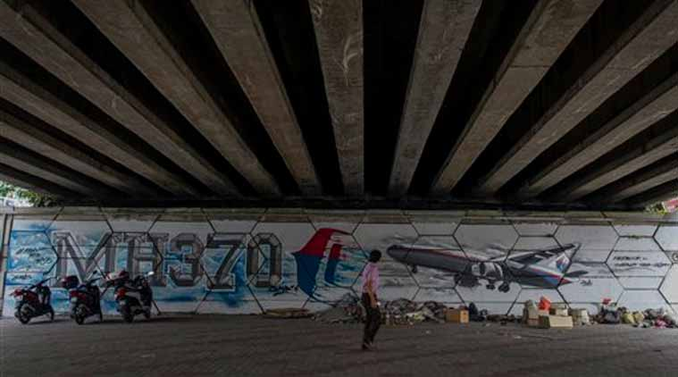 An unidentified man walks past MH370 related street art under a flyover in Kuala Lumpur, Malaysia on Friday, March 6, 2015. (Source: AP)