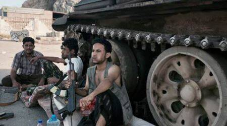 In this March 21, 2015, photo, Members of a militia group loyal to Yemen's President Abed Rabbo Mansour Hadi, known as the Popular Committees, chew qat as they sit next to their tank, guarding a major intersection in Aden, Yemen.