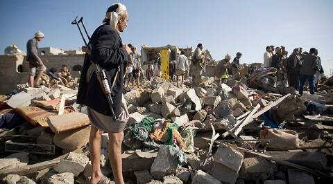 A Houthi Shiite fighter stand guard as people search for survivors under the rubble of houses destroyed by Saudi airstrikes near Sanaa Airport, Yemen, Thursday, March 26, 2015. (AP Photo)