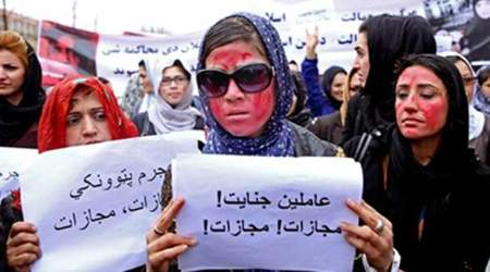 "Afghan women, demand justice for a woman who was beaten to death by a mob after being falsely accused of burning a Quran last week, during a protest in downtown Kabul, Afghanistan, Tuesday, March 24, 2015. Men and women of all ages carried banners bearing the bloodied face of Farkhunda, a 27-year-old religious scholar killed last week by a mob. Farkhunda, who went by one name like many Afghans, was beaten, run over with a car and burned before her body was thrown into the Kabul River. The poster at center with Persian writing reads, ""Farkhunda's murderers, execution."" (Source: AP)"