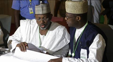 Independent National Electoral Commission chairman, Attahiru Jega, left, views election results at the coalition center in Abuja, Nigeria, Monday, March 30, 2015