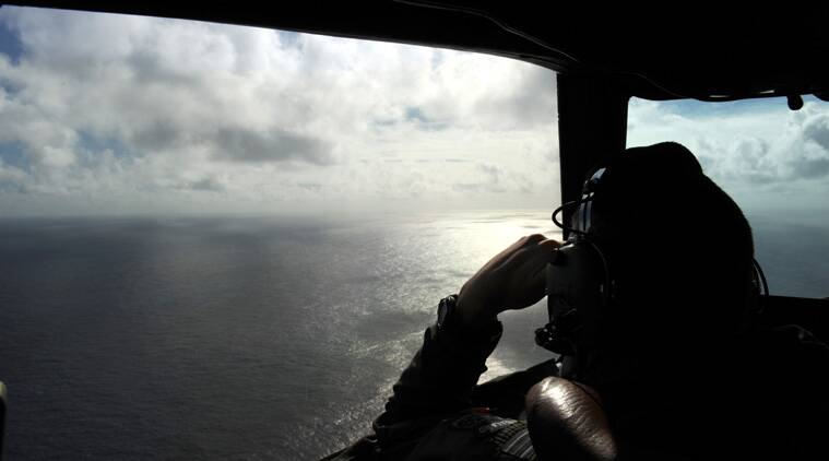 FILE - In this April 13, 2014 file photo taken from the Royal New Zealand air force (RNZAF) P-3K2-Orion aircraft, pilot and aircraft captain, Flight Lt. Timothy McAlevey looks out of a window while searching for debris from missing Malaysia Airlines Flight 370, over the Indian Ocean off the coast of western Australia. (AP Photo/Greg Wood, Pool, File)