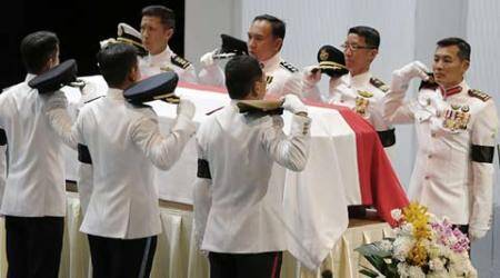 Pallbearers ready themselves by removing their headdress before carrying the coffin of the late Lee Kuan Yew during a state funeral held at the University Cultural Center, Sunday, March 29, 2015, in Singapore.