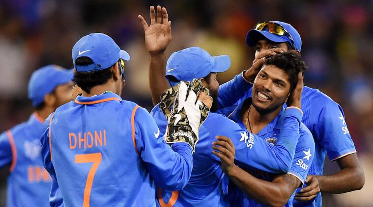 India's Umesh Yadav is embraced by teammate's as they celebrate the dismissal of Bangladesh's Mushfiqur Rahim during their Cricket World Cup quarterfinal match in Melbourne, Australia, Thursday, March 19, 2015.