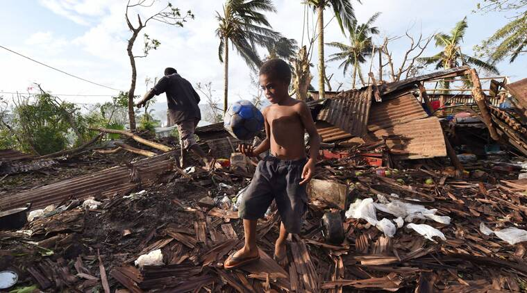 A boy  carries a ball through the rVanuatu,Vanuatu cyclone, cyclone pam, cyclone pam destruction, vanuatu relief, cyclone pam relief programme, united nations relief, WOrld NEwsuins of their family home as his father, Phillip, at back, picks through the debris in Port Vila, Vanuatu in the aftermath of Cyclone Pam Monday, March 16, 2015. (AP Photo)
