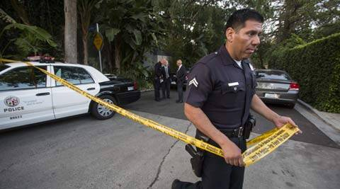 A police officer creates a perimeter outside a home in the Hollywood Hills area of Los Angeles, Tuesday, March 31, 2015.