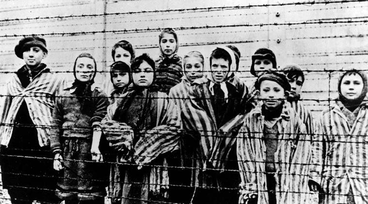 FILE - A picture taken just after the liberation by the Soviet army in January, 1945, shows a group of children wearing concentration camp uniforms behind barbed wire fencing in the Auschwitz Nazi concentration camp. One of the black-uniformed men on the ramp where people arrived was likely SS guard Oskar Groening who goes on trial Tuesday, April 21, 2015 in a state court in the northern city of Lueneburg on 300,000 counts of accessory to murder. (AP Photo/FILE)