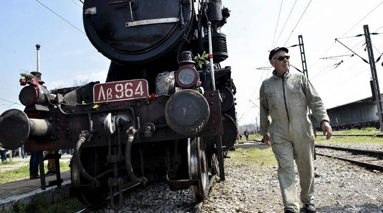 FILE - In this Sunday, March 15, 2015 file photo, a Hellenic Railway officer walks in front of a train that was used by the Nazis to carry Jews from Thessaloniki to Auschwitz during the WWII, in the Greek northern town of Thessaloniki, on the 72nd anniversary of the roundup and deportation of its Jews to Nazi extermination camps during World War II. It was 1943 and the Nazis were deporting Greece's Jews to Poland's death camps. Hitler's genocidal accountants reserved a chilling twist: The Jews had to pay their train fare. The total bill for 58,585 Jews sent to Auschwitz and other camps came to over 2 million Reichsmark - more than 25 million ($27 million) euros in today's money. The Jewish community of Thessaloniki, Greece's biggest, says it is examining the possibility of reclaiming the rail fares from Germany - and with seven decades of interest the amount would be enormous. (AP Photo/Giannis Papanikos,file)