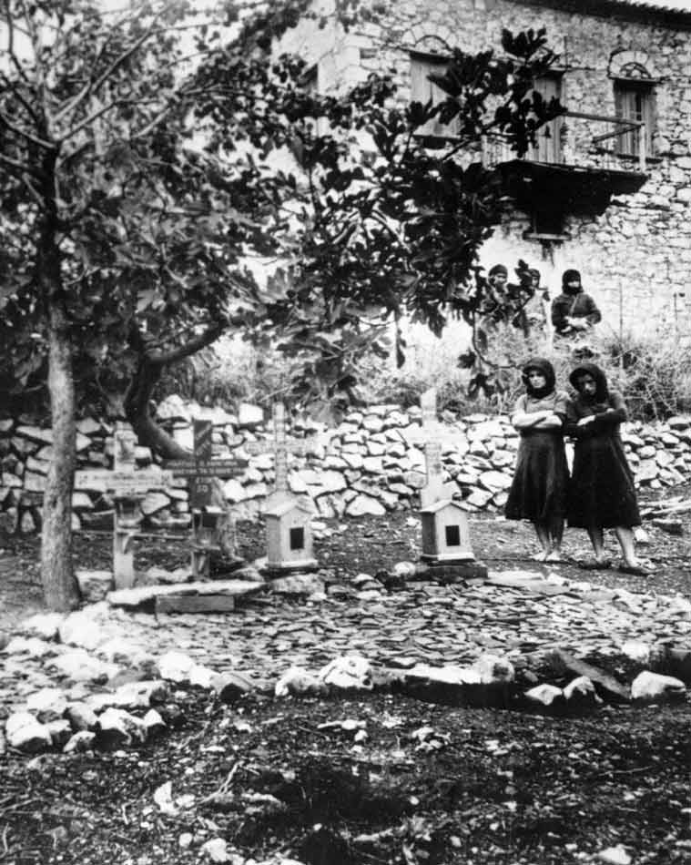 FILE - In this undated file picture, women stand in the graveyard of Distomo, Greece, where victims of a 1944 Nazi massacre are buried. In World War II German soldiers killed 214 people as punishment for an attack by partisans. It was 1943 and the Nazis were deporting Greece's Jews to Poland's death camps. Hitler's genocidal accountants reserved a chilling twist: The Jews had to pay their train fare. The total bill for 58,585 Jews sent to Auschwitz and other camps came to over 2 million Reichsmark - more than 25 million ($27 million) euros in today's money. The Jewish community of Thessaloniki, Greece's biggest, says it is examining the possibility of reclaiming the rail fares from Germany - and with seven decades of interest the amount would be enormous. (AP Photo, File)