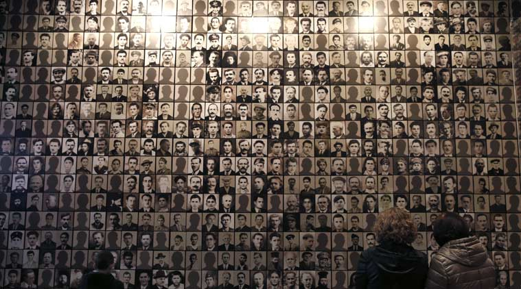 In this photo taken Saturday, March 21, 2015, visitors look at portraits of victims at the Holocaust Museum in the town of Kalavryta, western Greece. It was 1943 and the Nazis were deporting Greece's Jews to death camps in Poland. Hitler's genocidal accountants reserved a chilling twist: The Jews had to pay their train fare. The bill for 58,585 Jews sent to Auschwitz and other camps exceeded 2 million Reichsmark — more than 25 million euros ($27 million) in today's money. For decades, this was a forgotten footnote among all of the greater horrors of the Holocaust. Today it is returning to the fore amid the increasingly bitter row between Athens and Berlin over the Greek financial bailout. (AP Photo/Petros Giannakouris)
