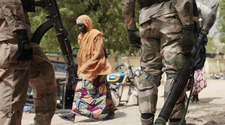 "In this photo taken Wednesday, April 8, 2015, a woman walks past Nigerian Soldiers at a checkpoint in Gwoza, Nigeria, a town newly liberated from Boko Haram. Each day brings new reports of atrocities, with mass graves being discovered in towns seized back from the militants who had set up a so-called ""Islamic caliphate"" across a great swath of northeast Nigeria. Boko Haram's nearly 6-year-old Islamic uprising in northeast Nigeria that has killed thousands — a reported 10,000 just last year — and forced more than 1.5 million from their homes. (AP Photo/Lekan Oyekanmi)"