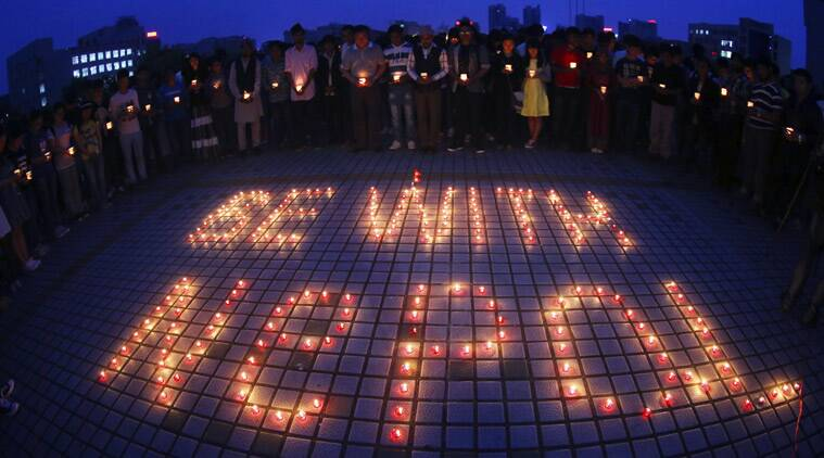In this Sunday, April 26, 2015 photo released by China's Xinhua News Agency, students light candles and pray for people trapped in Nepal earthquake at the University of South China in Hengyang City, central China's Hunan Province. (Source: AP photo)