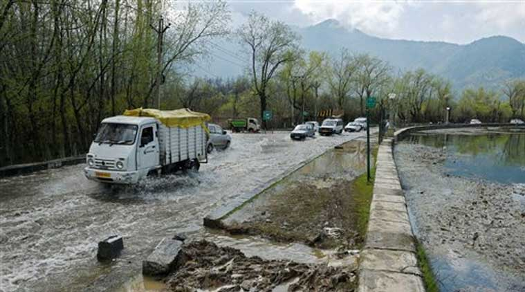 Vehicles move through the flooded road along the swollen Dal Lake in Srinagar on Saturday. (Source: PTI)