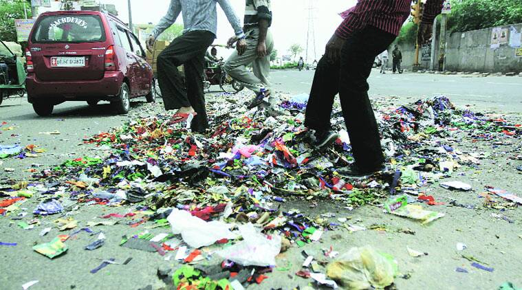 Sanitation workers spread garbage on a road in East Delhi on Tuesday. (Express photo by Praveen Khanna)