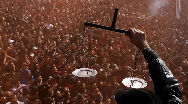 In this Jan. 26, 2013, file photo, an Egyptian soccer fan of Al-Ahly club displays scales to fans celebrating a court verdict that returned 21 death penalties in the previous year's soccer violence against their supporters in Port Said, inside the club premises in Cairo, Egypt.