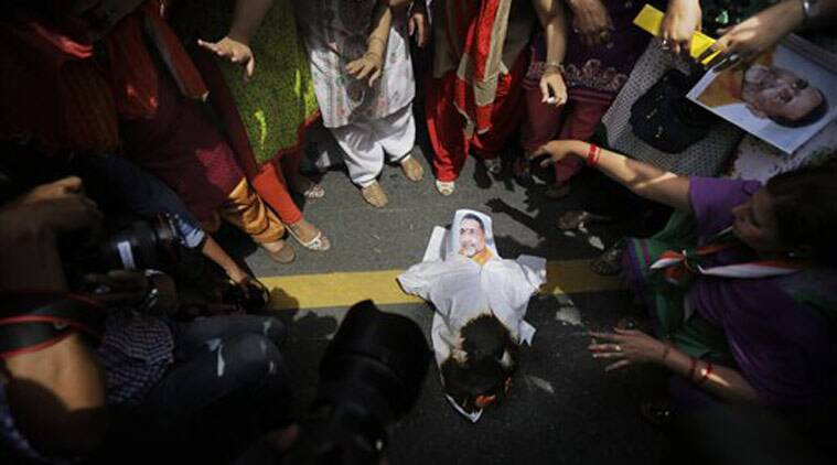 Activists of India's opposition Congress party's women's wing burn an effigy of Junior Indian Minister Giriraj Singh and shout slogans against the ruling Bharatiya Janata Party (BJP) during a protest outside the BJP headquarters in New Delhi. (Source: PTI)