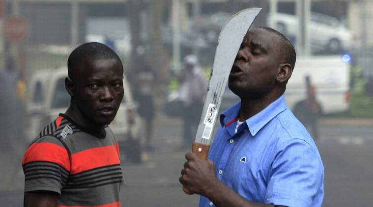 In this photo taken in Durban, South Africa, on Tuesday, April 14, 2015, an immigrant armed with a machete on a street during clashes with police and in search of locals that attacked foreign shop owners in the city center. (AP Photo/Tebogo Letsie)