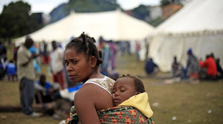 A woman makes her way through a refugee camp Wednesday, April 15, 2015, where more than 2,000 foreigners have sought shelter in Durban, South Africa after deadly attacks on immigrants . Five people have been killed and 74 people arrested since attacks began at the end of March (AP Photo/Tebogo Letsie)