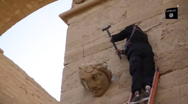 In this image made from a militant video posted on YouTube on Friday, April 3, 2015, which has been verified and is consistent with other AP reporting, a militant fires his weapon at faces on a wall in Hatra, a large fortified city recognized as a UNESCO World Heritage site, 110 kilometers (68 miles) southwest of Mosul, Iraq. (AP Photo)