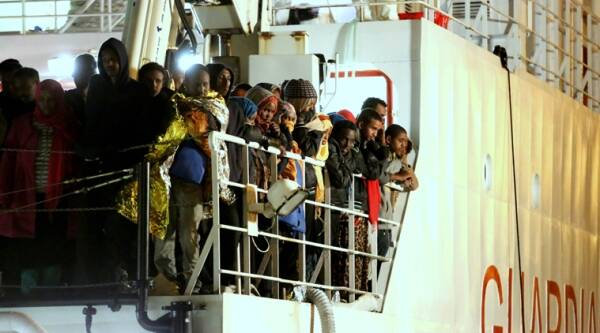 File - Rescued migrants wait to disembark from an Italian Coast Guard ship in the harbor of Palermo, Sicily, southern Italy, Tuesday, April 14, 2015. The European Union says that more than 7,000 migrants have been plucked from the Mediterranean since Friday as an unprecedented wave of people flee conflict and poverty seeking better lives in Europe. (AP Photo)