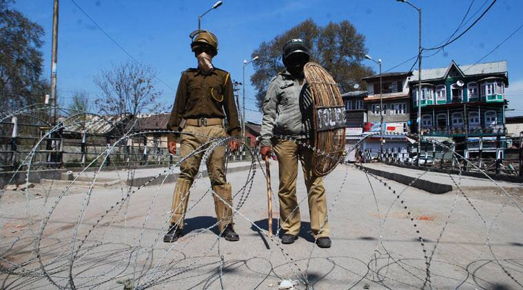 Security personnel stands guard infront of closed shops during Strike in Srinagar. (Source: Express photo by Shuaib Masoodi)
