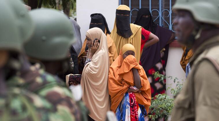 Women look across as Kenya Defence Forces (KDF) soldiers arrive at a hospital to escort the bodies of the attackers to be put on public view, in Garissa, Kenya Saturday, April 4, 2015. (Source: AP)