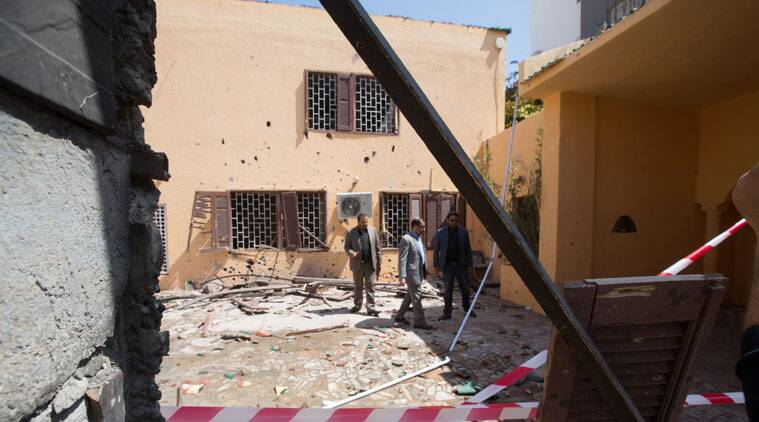 Officials survey the grounds of the the Moroccan Embassy in Tripoli, Libya after a bomb left in a garbage bin exploded on Monday, April 13, 2015. There were no casualties in the attack, which was claimed by Libya's Islamic State affiliate. (AP Photo/Mohamed Ben Khalifa)