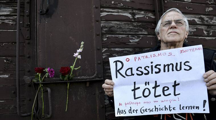 "FILE - In this March 15, 2015 file photo a man holds a banner which reads ""Racism Kills, Let's Learn From the History"", in front of a train wagon that was used by the Nazis to carry Jews from Thessaloniki to Auschwitz during WWII, in the Greek northern town of Thessaloniki, on the 72nd anniversary of the roundup and deportation of its Jews to Nazi extermination camps during World War II. It was 1943 and the Nazis were deporting Greece's Jews to Poland's death camps. Hitler's genocidal accountants reserved a chilling twist: The Jews had to pay their train fare. The total bill for 58,585 Jews sent to Auschwitz and other camps came to over 2 million Reichsmark - more than 25 million ( million) euros in today's money. The Jewish community of Thessaloniki, Greece's biggest, says it is examining the possibility of reclaiming the rail fares from Germany - and with seven decades of interest the amount would be enormous. (AP Photo/Giannis Papanikos, File)"