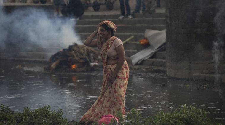 A woman weeps during the cremation of a victim of Saturday's earthquake, at the Pashupatinath temple, on the banks of Bagmati river, in Kathmandu, Nepal, Sunday, April 26, 2015.  (AP Photo)
