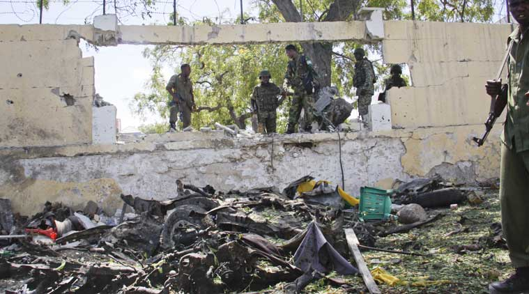 Soldiers stand near the wreckage of a car bomb that was detonated at the gates of a government office complex in the capital Mogadishu, Somalia, on Tuesday. (Source: AP photo)