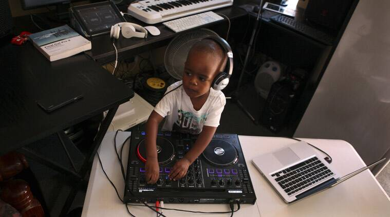 Oratilwe Hlongwane plays with the buttons and knobs of a sophisticated music system in control of the beat of the bass-heavy house music at his Alexandra home in Johannesburg. (Source: AP photo)
