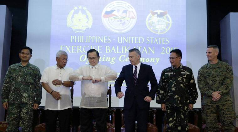 U.S. and Philippine officials, from left, Vice-Admiral Alexander Lopez, co-chair of this year's annual joint Philippines-U.S. Balikatan 2015 military exercise, Philippine Defense Chief Voltaire Gazmin, Philippine Foreign Affairs Undersecretary Evan Garcia, U.S. Ambassador to the Philippines Philip Goldberg, Philippine Armed Forces Chief Gen. Gregorio Pio Catapang and co-chair Brig. Gen. Christopher Mahoney, prepare to link arms at the opening ceremony Monday, April 20, 2015 at Camp Aguinaldo at suburban Quezon city, northeast of Manila, Philippines. More than ten thousand troops from both countries' militaries are taking part in the annual military drill that focuses on regional security, terrorism, disaster preparedness and inter-operability of both countries. (AP Photo/Bullit Marquez)