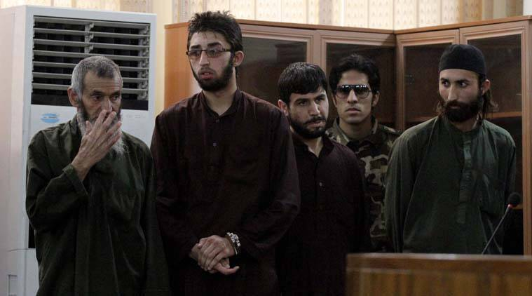 Defendants are guarded by a security official, second left, as they attend their trial at the Primary Court, in Kabul, Afghanistan, Wednesday, May 6, 2015. An Afghan judge has convicted and sentenced the four men to death for their role in the brutal mob killing of a woman in Kabul in March. The judge announced the sentences Wednesday as part of a trial of 49 suspects, including 19 police officers. He also sentenced eight defendants to 16 years in prison and dropped charges against 18. The remaining suspects are to be sentenced on Sunday. (AP Photo/Allauddin Khan)