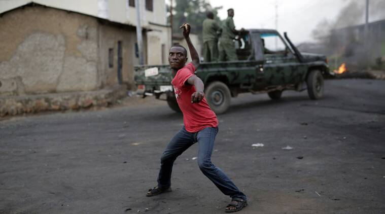 A demonstrator throws a stone at Burundi riot police as a Burundi military truck drives by in Bujumbura, Burundi, Wednesday April 29, 2015. Protesters were again on the streets Wednesday, angry over the Burundian president's third term bid that they say is unconstitutional as a top U.S. diplomat headed to the East African nation. (AP Photo/Jerome Delay)
