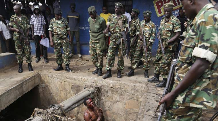 Jean Claude Niyonzima, a suspected member of the ruling party's Imbonerakure youth militia, pleads with soldiers to protect him from a mob of demonstrators after he came out of hiding in a sewer in the Cibitoke district of Bujumbura, Burundi, Thursday May 7, 2015. Niyonzima fled from his house into the sewer under a hail of stones thrown by a mob protesting President Pierre Nkurunziza's decision to seek a third term in office. At least one protestor has died in clashed with the widely feared Imbonerakure militias and police, sending scores to the streets seeking revenge. (AP Photo/Jerome Delay)