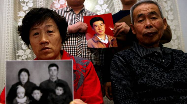 In this Dec. 16, 2014 photo, brothers of Huugjilt, a wrongly executed man, hold a photo of him, at rear, while his parents, in front, hold a family photo in Hohhot in northern China's Inner Mongolia Autonomous Region. Huugjilt, who was 18 when he was convicted and executed in 1996 on charges of rape and murder, was formally exonerated by the Chinese government in Dec. 2014, and the police officer who oversaw the original case has been charged with using torture to coerce a confession. In a report released Wednesday, May 13, 2015, Human Rights Watch says that police abuse in order to extract confessions continues to be a serious problem despite measures to reform the legal system. (Chinatopix Via AP) CHINA OUT