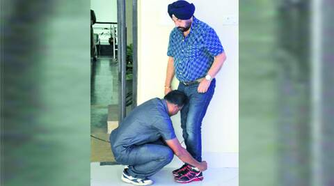 A security guard ties the shoes of Planning Minister Rachpal Singh at Nabanna on Monday. (Source: Express Photo)