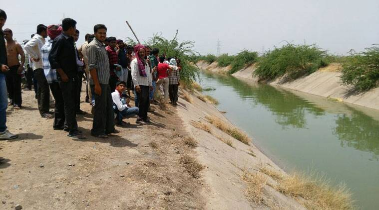 People gather on the bank of the canal where three people were feared drowned. (Source: Express photo)