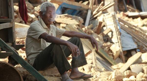 In this photo taken on Saturday, May 2, 2015, Fattha Bahadur Rana, 90, has a smoke as he sits in the rubble of his collapsed home in the destroyed village of Pokharidanda, near the epicenter of the April 25 massive earthquake, in the Gorkha District of Nepal. (AP Photo)