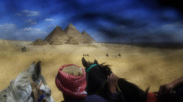 This Thursday, April 9, 2015 photo shows a man leading tourists riding horses at the historical site of the Giza Pyramids near Cairo. This photo was shot through the lowered veil of a niqab, which is worn by some conservative Muslim women. The cloth allows women to follow a strict interpretation of their religious beliefs by preventing others from seeing their faces. (AP Photo/Hassan Ammar)