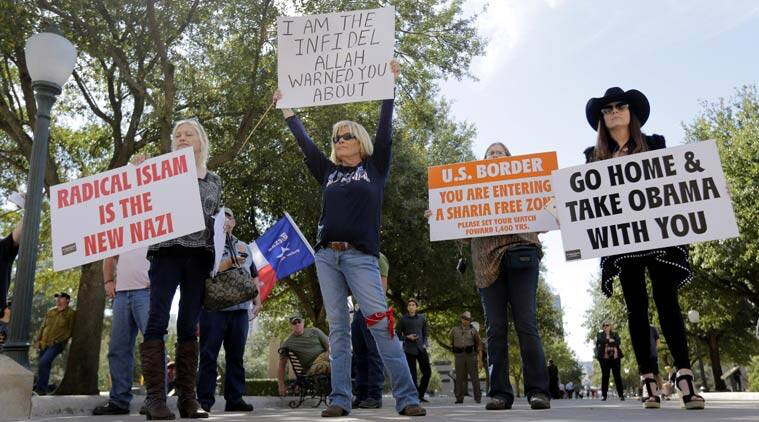 Protesters hold signs and yell to disrupt and heckle a group gathered for a Texas Muslim Capitol Day rally, in Austin, Texas. (Source: AP)