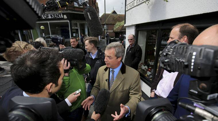UK Independence Party leader Nigel Farage, centre, talks to the media while he meets supporters canvassing for support during a walk about in Sandwich, England, as he continues his election campaign trail, Tuesday May 5, 2015. Britain's political candidates are campaigning all across Britain in search of votes ahead of the May 7 General Election, just two days away. (Gareth Fuller / PA via AP)