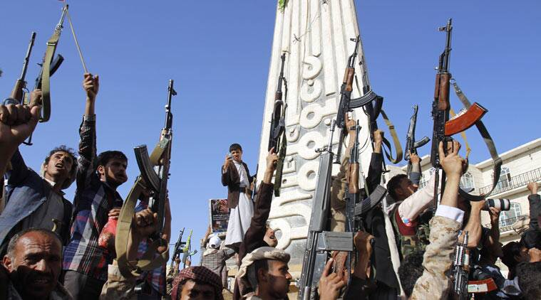 A Yemeni man, background, uses his mobile to take photos of Shiite rebels, known as Houthis, holding up their weapons during a demonstration against an arms embargo imposed by the U.N. Security Council on Houthi leaders, in Sanaa, Yemen, Thursday, April 16, 2015. Al-Qaida's branch in Yemen seized Thursday control of a major airport and sea port and oil terminal in southern Yemen, consolidating their hold of the country's largest province amid wider chaos that is pitting Shiite rebels against forces loyal to the country's exiled president and a Saudi-led air campaign.(AP Photo/Hani Mohammed)