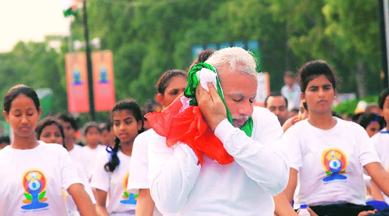 Prime Minister Narendra Modi wipes his face amid the exertion in the open. (Source: Express photo by Neeraj Priyadarshi)