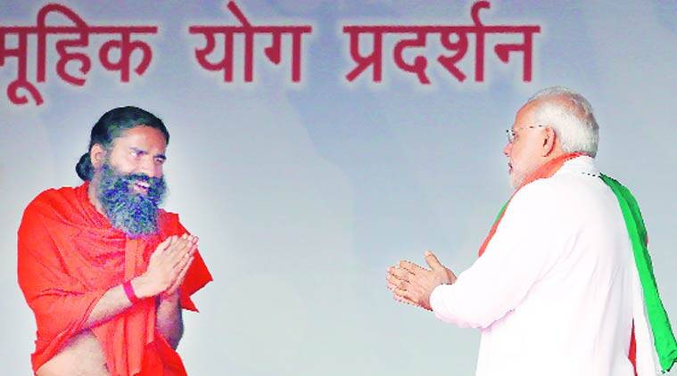 Earlier, PM Narendra Modi greets Baba Ramdev on stage after his arrival; the latter presented him a copy of his Encyclopaedia of Yoga. (Source: Express photo by Ravi Kanojia)